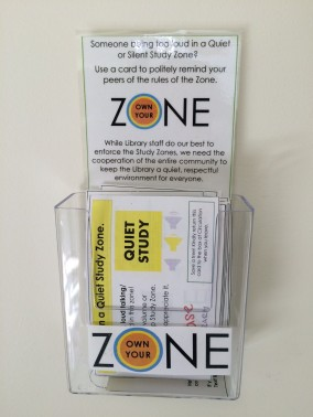 photo of plastic holder on wall with own your zone cards