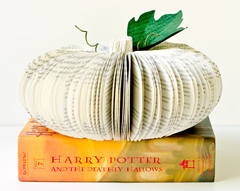 decorative pumpkin made of white book pages on top of Harry Potter and Deathly Hallows book